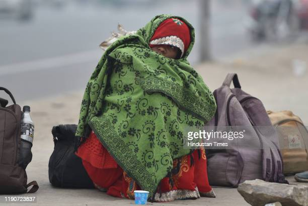 Woman waits for a passenger bus wearing warm clothes on a cold morning, at Sarai Kale Khan, on December 29, 2019 in New Delhi, India. Severe cold...
