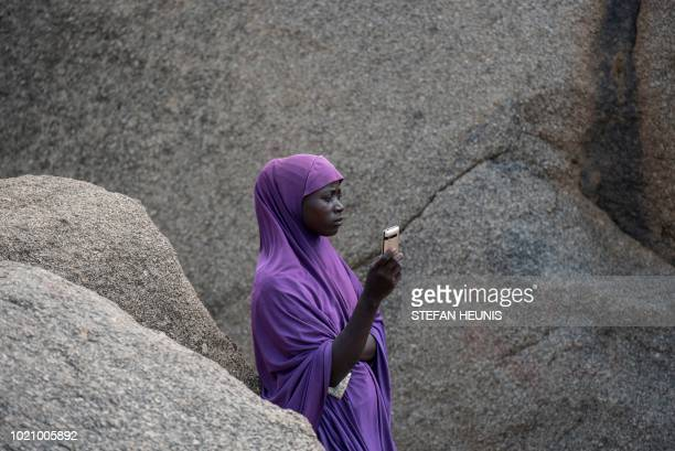 A woman waits for a phone call on the only hill in Pulka that receives cellphone signal on August 1 2018 As the presidential race heats up ahead of...