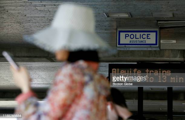 Woman waits for a Red Line train at the JFK/UMass station in the Dorchester neighborhood of Boston as the board behind her advises that trains will...