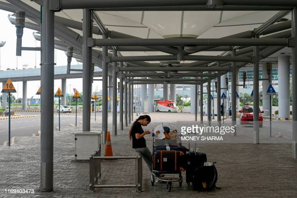 A woman waits for a taxi outside Indira Gandhi International airport in New Delhi on September 19 as road transport services have called for a oneday...