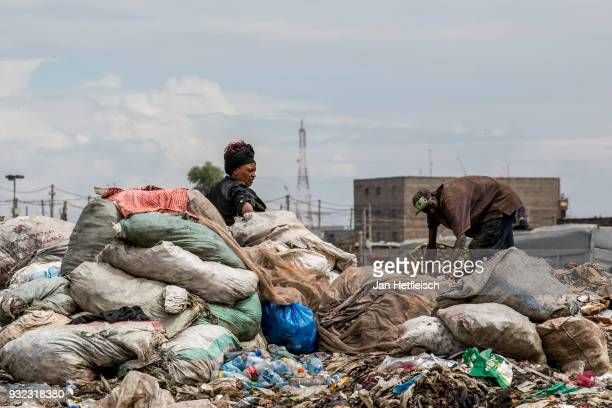 A woman waits for an empty truck to bring plastic bottles to a recycling company on March 14 2018 in Nairobi Kenya The Dandora landfield is located 8...
