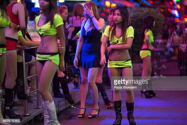 A woman waits for business in the red light district called ' Soi Cowboy' as sex tourism continues despite the curfew May 26 2014 in Bangkok Thailand...