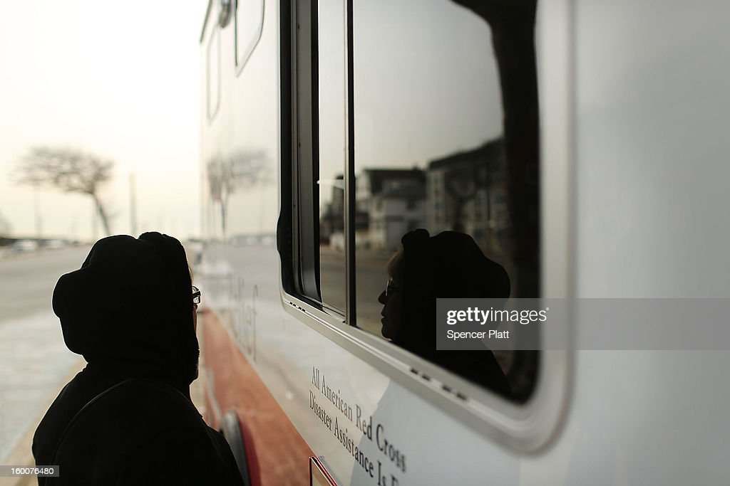 A woman waits for food at the window of Red Cross Disaster Relief truck in the Rockaways following Hurricane Sandy on January 25, 2013 in the Queens borough of New York City. Three months after Sandy devastated parts of New York and New Jersey, hundreds of residents are still without electricity and heat and depend on churches and charities to meet their basic needs. This past week saw some of the coldest temperatures of the winter hit parts of New York.