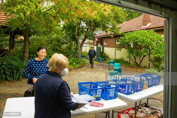 A woman waits for food items at St Paul's Anglican Church in Burwood on March 24 2020 in Sydney Australia The Parish Pantry provides food for the...