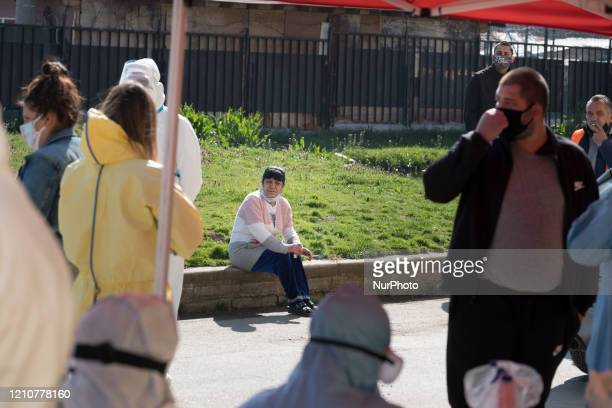 A woman waits for her fast antibody test results Medical workers set up free antibody and COVID19 testing at the entrance to the primary school in...