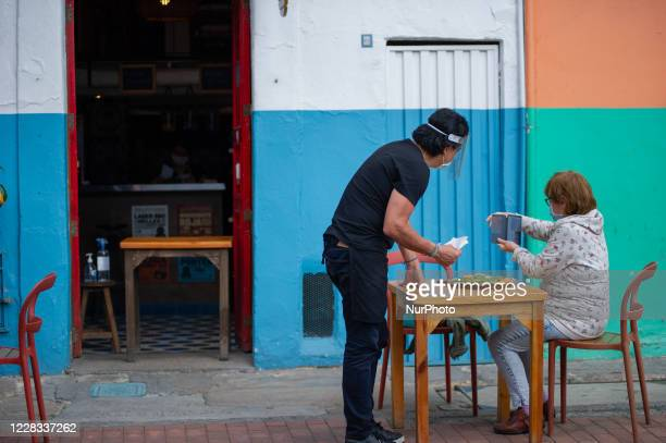 A woman waits for her lunch outiside of a restaurant located in the Candelaria neighboorhood as part of the pilot to re open restaurants Bogota Open...