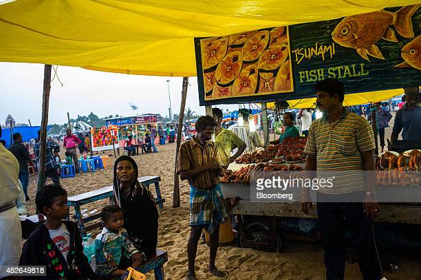 A woman waits for her order at a fried fish stall on Marina Beach in Chennai Tamil Nadu India on Sunday July 20 2014 Optimism about a revival in...
