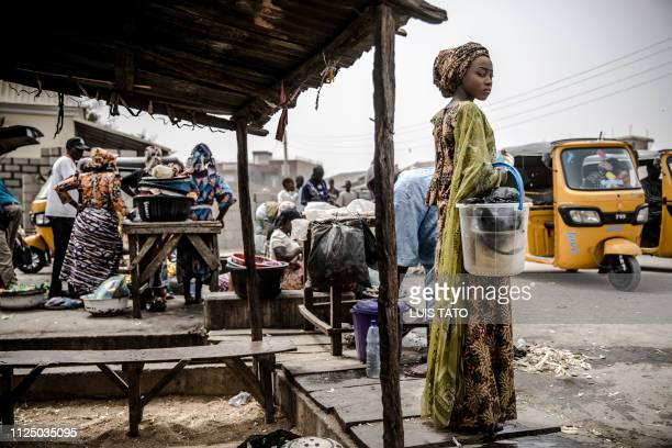 A woman waits for her taxi after shopping at a market which was attacked last year by Boko Haram Islamists in the Nigerian city of Mubi Adamawa State...