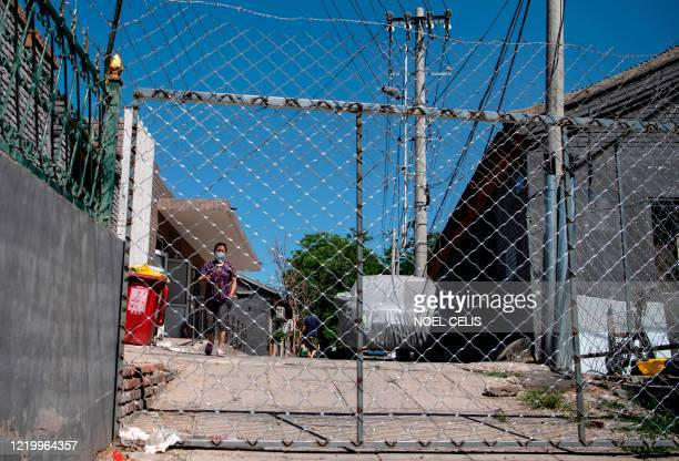 A woman waits for the delivery of goods she ordered online in the Yilanyuan residential area which is under lockdown after a new COVID19 coronavirus...