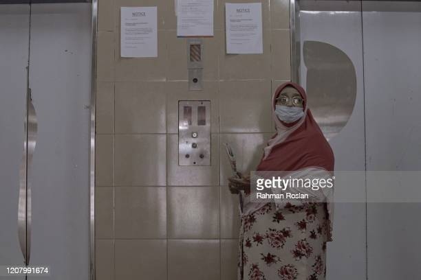 A woman waits for the elevator of a housing complex during Movement Control Order on March 23 2020 in Kuala Lumpur Malaysia Prime Minister Tan Sri...