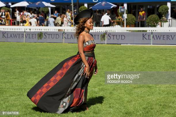 A woman waits for the start of the Met horse race at Kenilworth race track on January 27 in Cape Town The Met is one of South Africa's premier horse...