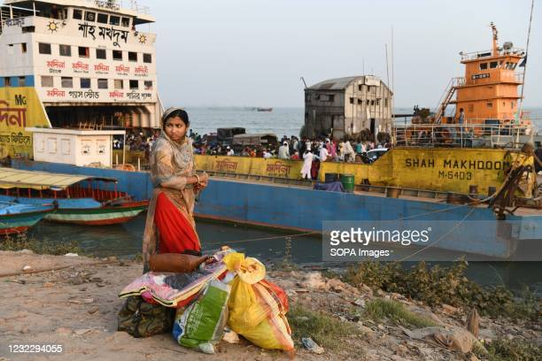 Woman waits for the truck to return home before lockdown at Mawa Ferry terminal near Dhaka. Bangladesh extends nationwide lockdown measures until...