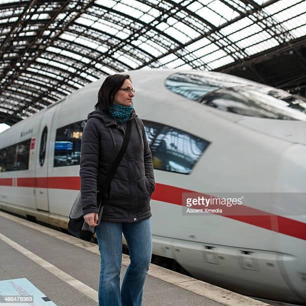 Woman waits for train on station platform