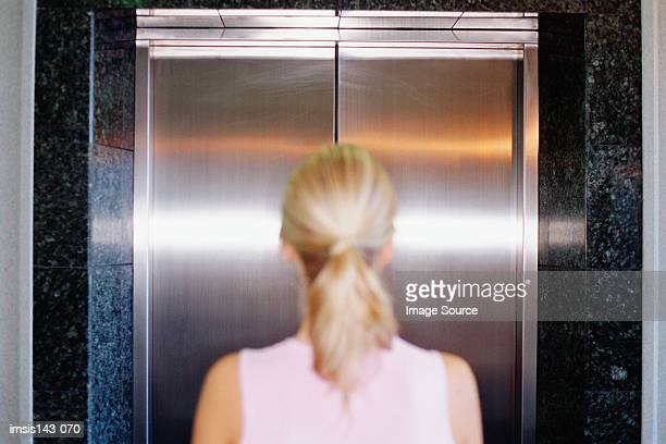 Woman waits in front of lift