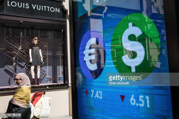 A woman waits in line outside a Louis Vuitton store to take advantage of low prices due to the exchange rate on August 14 2018 in Istanbul Turkey The...