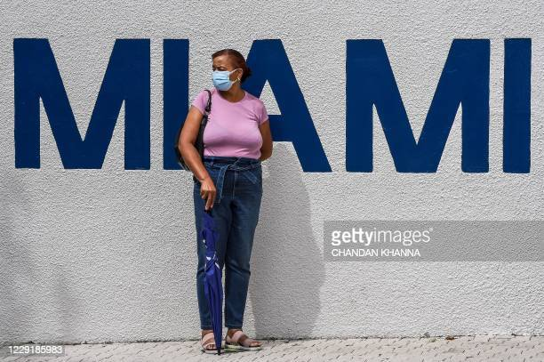 Woman waits in line to cast her early ballot at Miami Beach City Hall in Miami Beach, Florida on October 20, 2020. - With two weeks to go until...