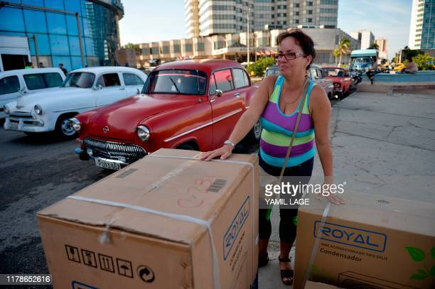 A woman waits next to home appliances boxes after buying them in Havana on October 28 2019 A program to sell highdemand appliances in dollars started...