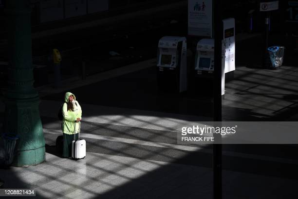 Woman waits past her suitcase at Gare du Nord in Paris on April 1 on the sixteenth day of a lockdown in France aimed at curbing the spread of the...