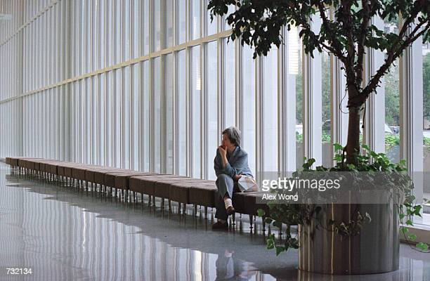 A woman waits September 19 2000 at the lobby of the World Bank headquarters main complex in Washington