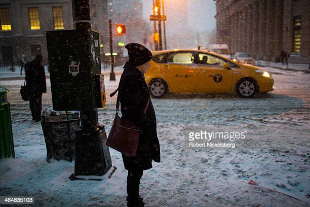 Woman waits to cross an intersection near the Borough Hall subway station during a snow storm on January 21, 2014 in the Brooklyn borough of New York...
