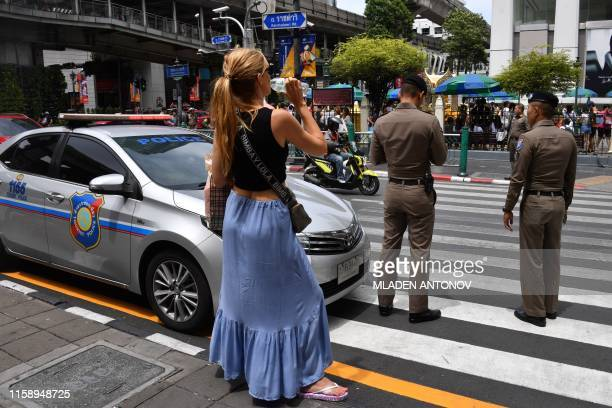 A woman waits to cross the road to the Erawan Shrine an area popular with tourists as police are seen in Bangkok on August 2 after several small...