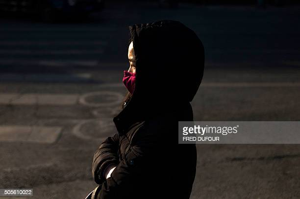 TOPSHOT A woman waits to cross the street in Beijing on January 19 2016 China's economy grew at its slowest pace in a quarter of a century last year...