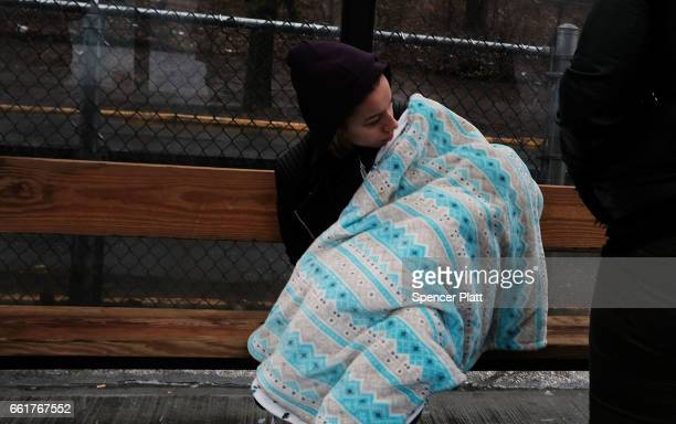 A woman waits with her child to board a bus to Rikers Island on March 31 2017 in New York City New York Mayor Bill de Blasio has said that he agrees...