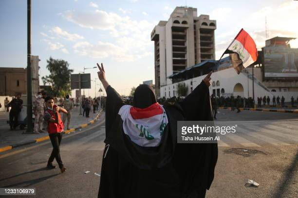 Woman waiving Iraqi flag and trying to stop Riot police after rushing towards protesters on May 25, 2021 in Baghdad, Iraq. Protesters from across the...