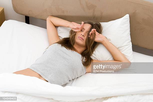 Woman waking in bed, covering eyes