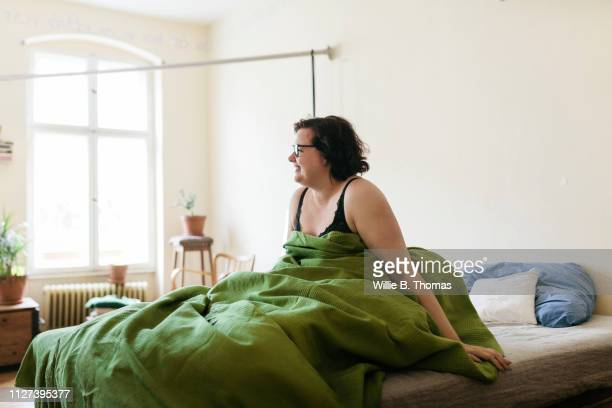 woman waking up in bed - waking up stock pictures, royalty-free photos & images