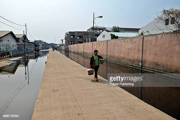 Woman walk along a road surrounded by a constant pool of water in the Maura Baru district, seen on November 30, 2015 in Jakarta, Indonesia. Jakarta,...