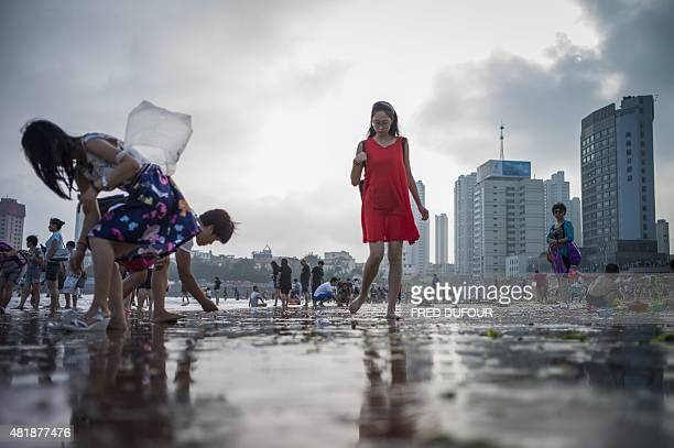 A woman walk at the beach in Qingdao eastern China's Shandong province on July 24 2015 AFP PHOTO / FRED DUFOUR