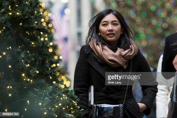 A woman walk by Christmas decorated trees along Rockefeller Center on Christmas day on December 25 2017 in New York City Security in New York is on...