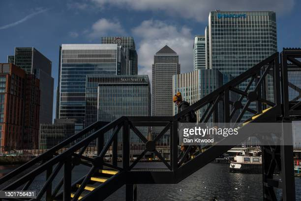 Woman walk her dog over a bridge near the Canary Wharf business district on February 12, 2021 in London, England. The ONS figures released today show...