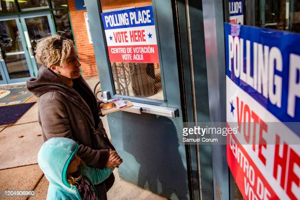 A woman walk into the polling location with her daughter at Taylor Elementary School to cast her ballot in the Democratic presidential primary...