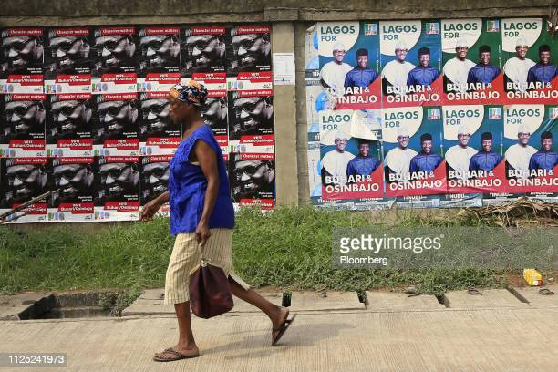 A woman walk pass campaign posters of Muhammadu Buhari Nigeria's president and candidate of the ruling All Progressives Congress party in Lagos...
