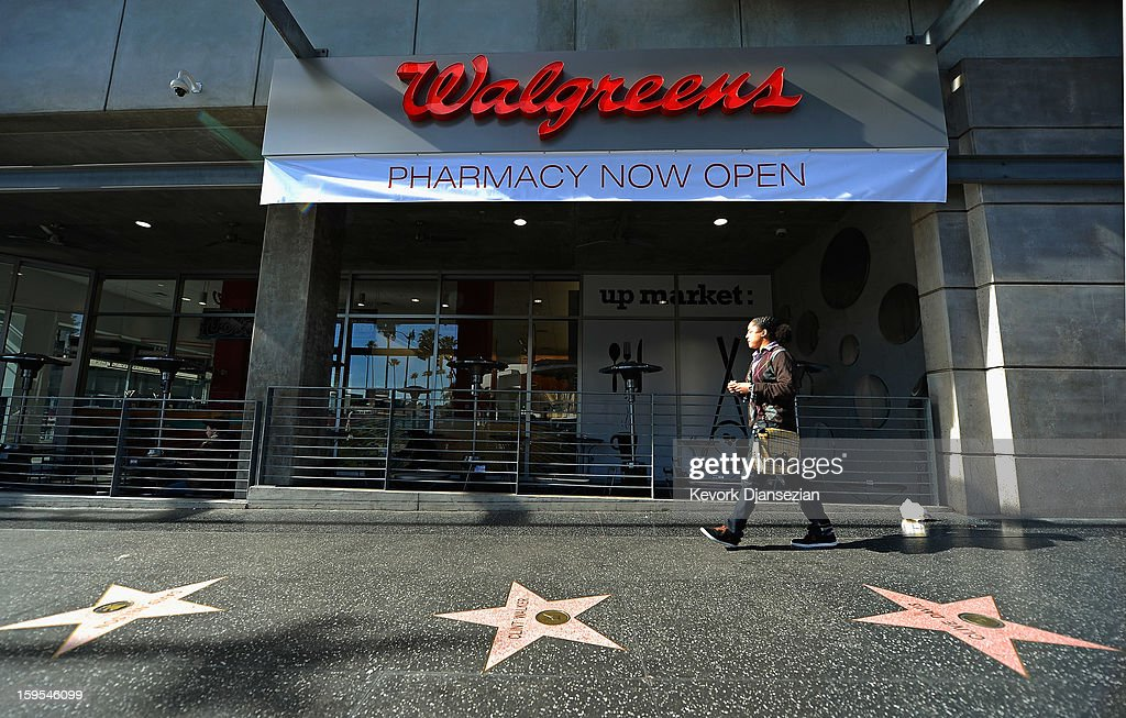 A woman walk past a new Walgreens at the corner of Sunset and Vine on January 15, 2013 in Hollywood, California. The new 23,500-square-foot, drugstore, the company's 8,000th store and first West Coast flagship, includes high-end cosmetic, skinand hair care brands, a frozen yogurt station, a fresh sushi bar, a coffee and espresso bar, a juice and smoothie bar, a wine and spirits shop with a and a virtual bartender kiosk and a cigar humidor.