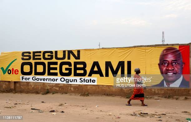 A woman walk past long campaign banner bearing photograph of former captain of Nigerian national football team the Super Eagles Segun Odegbami who is...