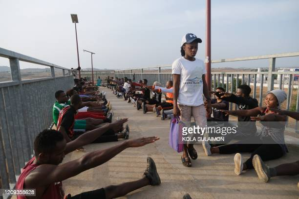 A woman walk past people partaking in a public fitness programme on a pedestrian bridge as authorities continue a 14day lockdown in a bid to contain...
