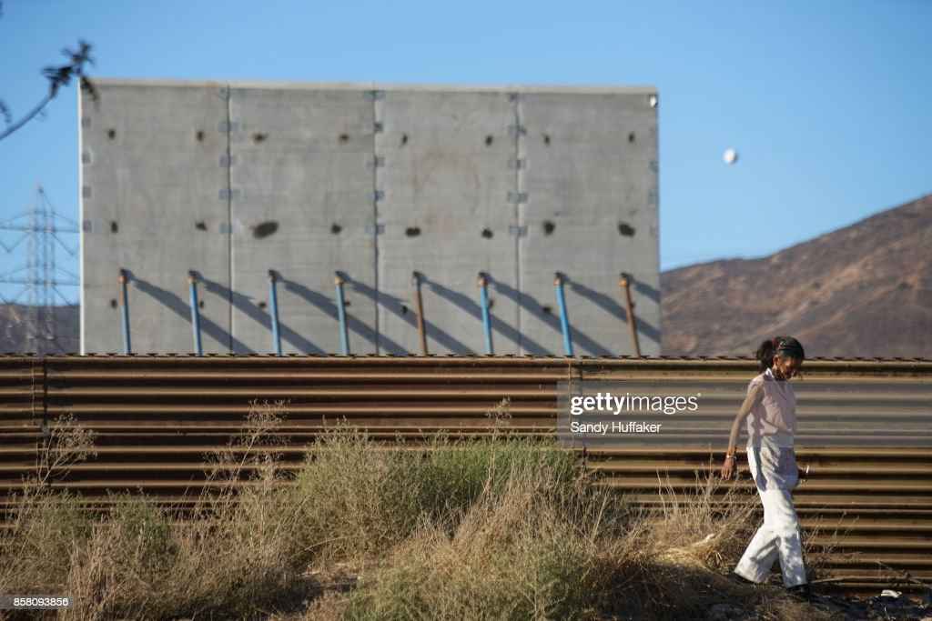 A woman walk past prototype sections of a border wall between Mexico and the United States under construction on October 5, 2017 in Tijuana, Mexico. Prototypes of the border wall propopsed by President Donald Trump are being built just north of the U.S.- Mexico border, where competitors who are hoping to gain approval to build the wall have until the first of next month to complete their work.