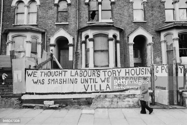 A woman walk pasts squatted houses on Villa Road Lambeth London UK 28th April 1977 In front of the buildings a slogan says 'We thought Labour's Tory...