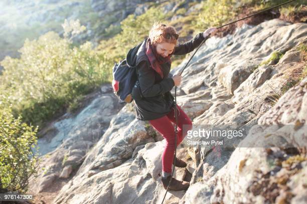 Woman walkind down in mountains, hanging on rope