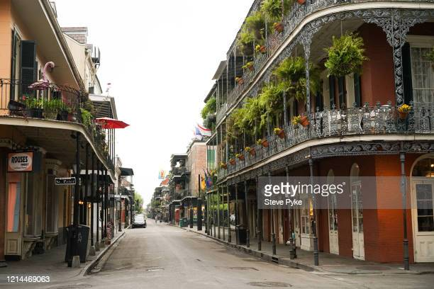 A woman walking a dog on a neardeserted Royal Street street seen from the corner with St Peter Street in the French Quarter of New Orleans amid...