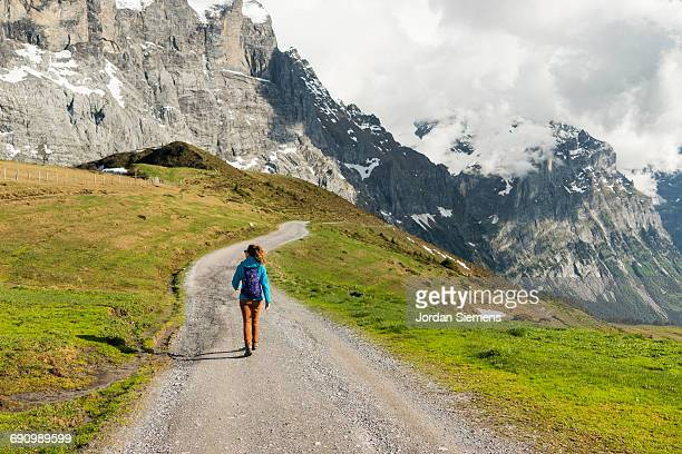 A woman walking a road in the mountains.