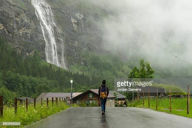 A woman walking a wet road