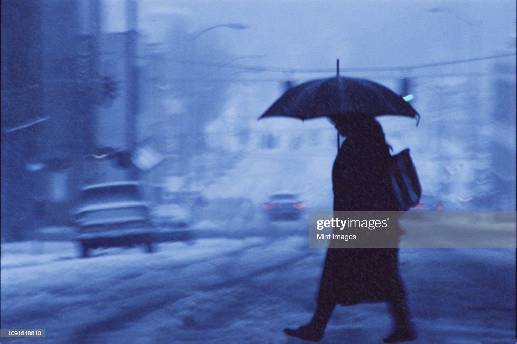 A woman walking across a city street covered in snow and rain in the winter. : Stock Photo