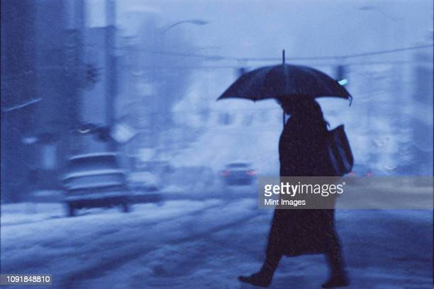 a woman walking across a city street covered in snow and rain in the winter. - sleet stock photos and pictures