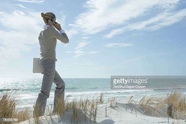 Woman walking across dunes, using cell phone, carrying laptop under arm