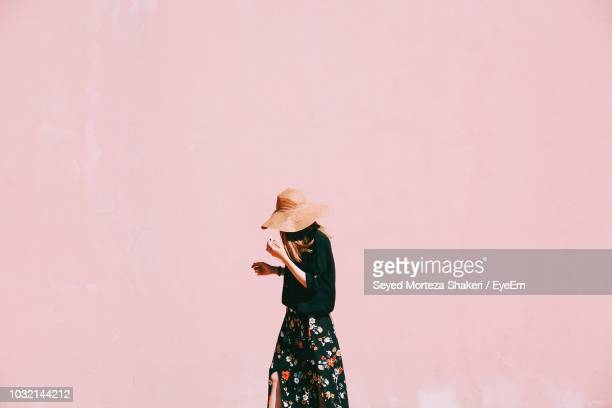 woman walking against pink wall - pink hat stock pictures, royalty-free photos & images