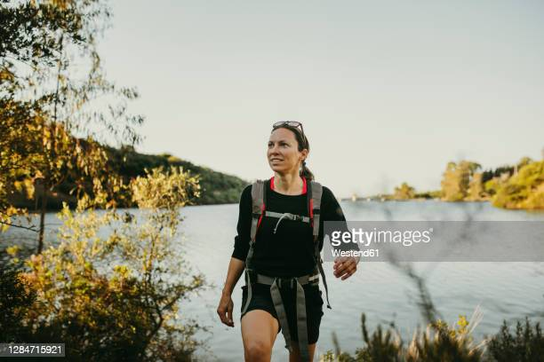 woman walking against river by sierra morena mountain at sierra de hornachuelos, cordoba, spain - andalucia stock pictures, royalty-free photos & images